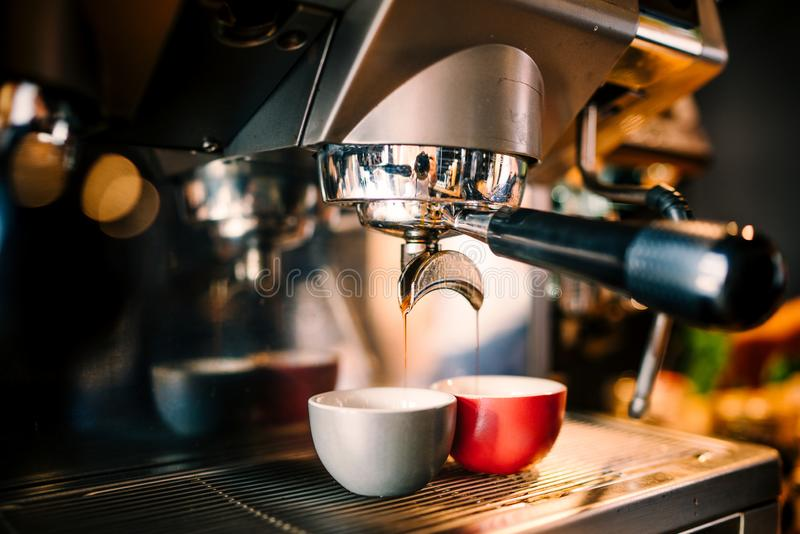 Details of brewing machinery pouring and preparing espresso in two cups. Cafe shop details. Close up details of brewing machinery pouring and preparing espresso royalty free stock photo