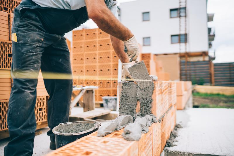 details of industrial bricklayer installing bricks on building construction site royalty free stock images