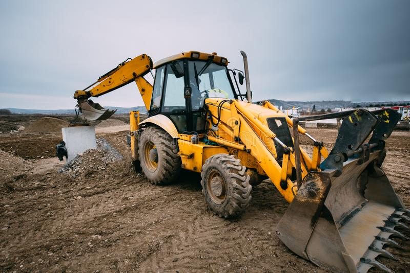 Close up details of massive working machinery, industrial backhoe loader with excavator on construction site royalty free stock photos
