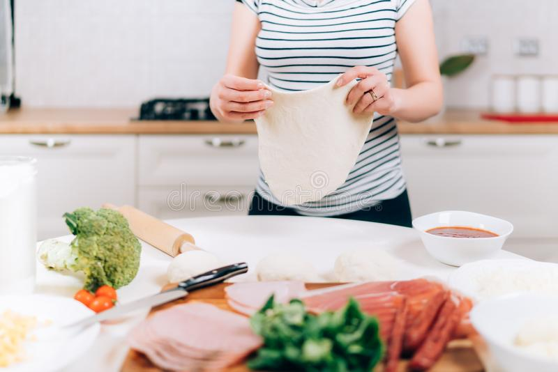 Close up details of pregnant woman preparing pizza and making dough stock photo
