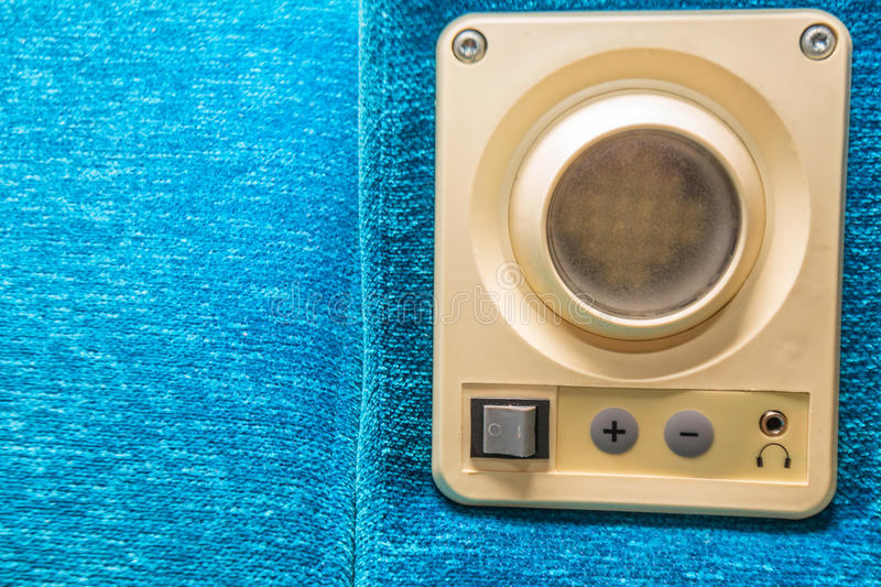 Close up device mounted in train seat. Small white plastic device with socket for headphones and control buttons installed in train compartment seat stock photography