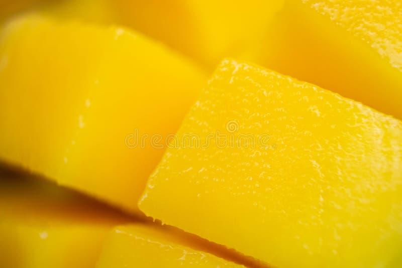 Close up dice yellow mango cut into cubes. Macro shot background. Rip exotic tropial fruit slice stock photo