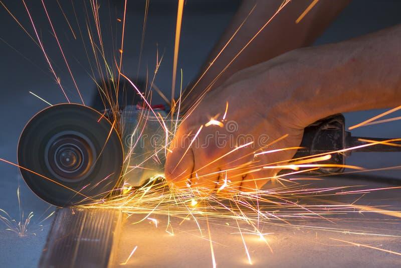 Close-up die van arbeidershanden metaal met molen snijden Vonkt whil stock foto's