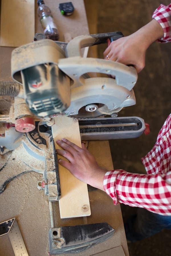 close-up die van blad is ontsproten Timmerman Using Circular Saw voor hout, houtbewerking stock fotografie