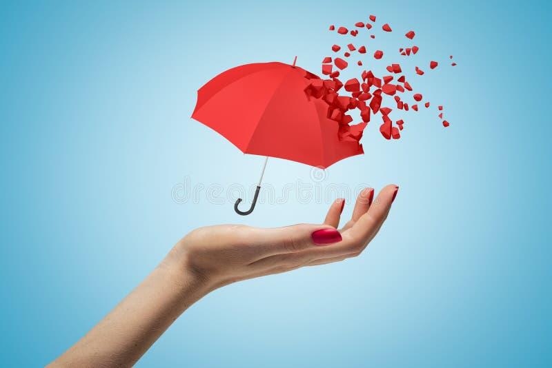 Close-up die van de hand van de vrouw omhoog en kleine rode paraplu onder ogen zien levitatie ondergaan die reeds het oplossen in stock fotografie