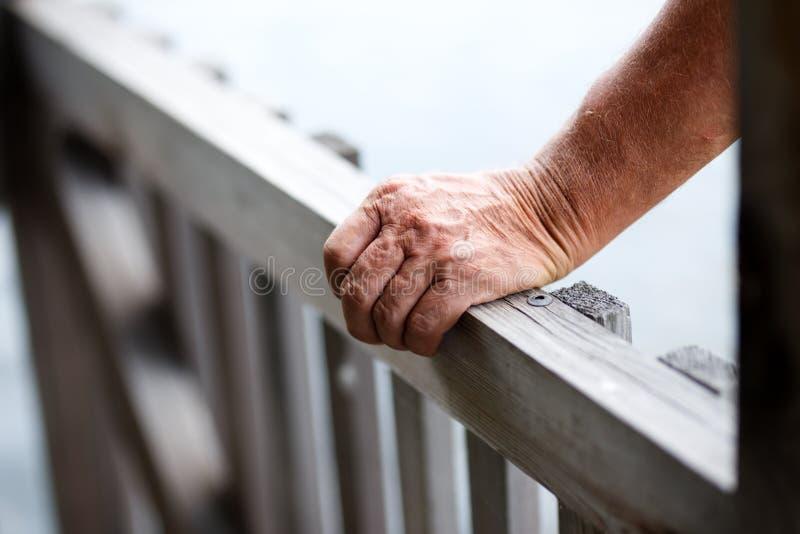 Close-up die van de oude mens zich dichtbij houten omheining bevinden terwijl het zetten van hand op traliewerk royalty-vrije stock foto's