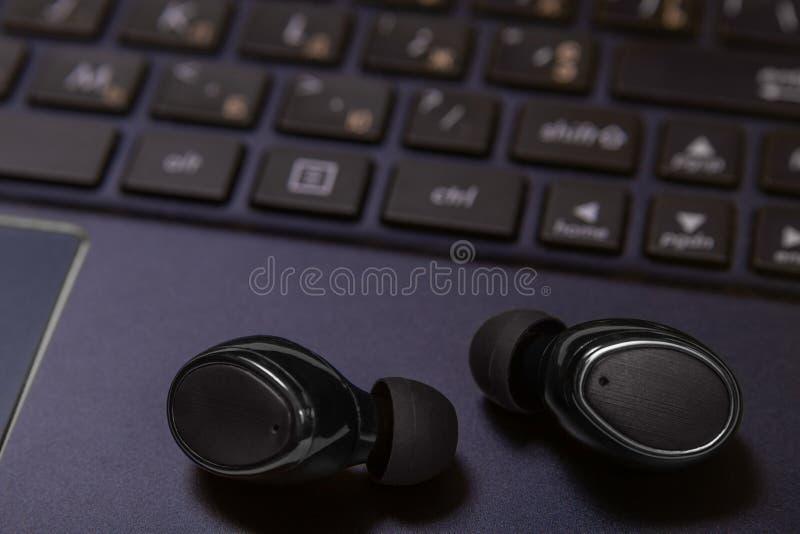 Close-up die van draadloze oortelefoons op een laptop toetsenbord liggen royalty-vrije stock afbeelding