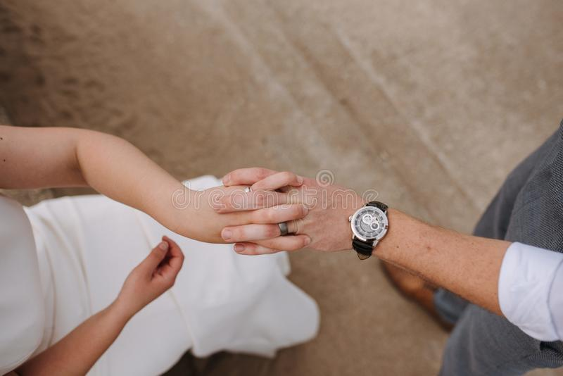 Close-up die van een mannelijke en vrouwelijke holdingshanden wordt geschoten op een bruine achtergrond stock foto