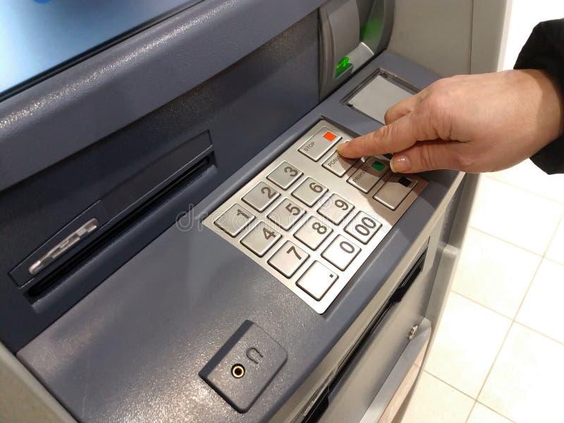 Close-up die van hand PIN/pass-code inzake ATM/bank-machinetoetsenbord ingaan stock foto