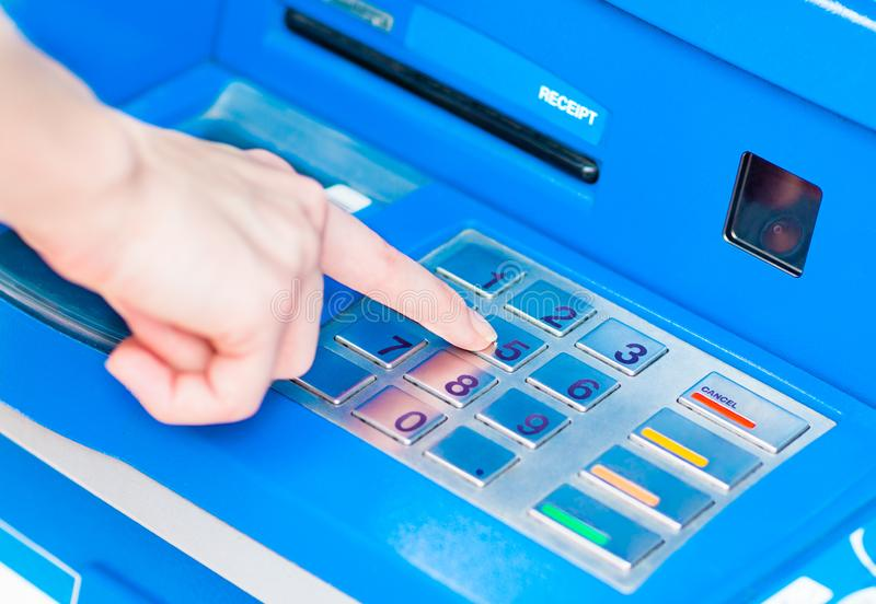 Close-up die van hand PIN/pass-code inzake blauw ATM/bank-machinetoetsenbord ingaan royalty-vrije stock fotografie