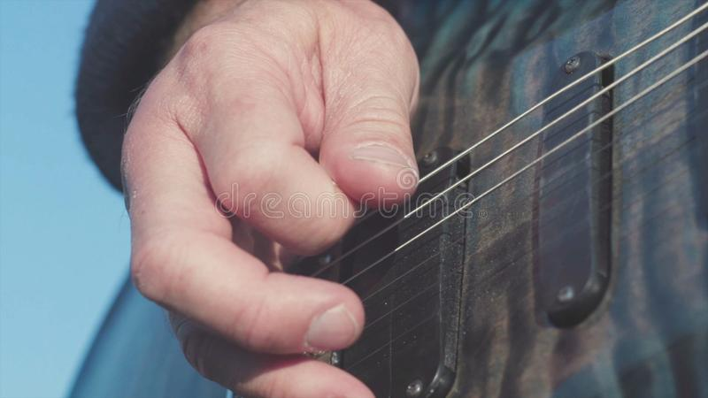 Close-up die van handen basgitaar spelen voorraad Mannelijke handen van gitarist het spelen snaren op basgitaar uitgevoerde muzie royalty-vrije stock afbeeldingen