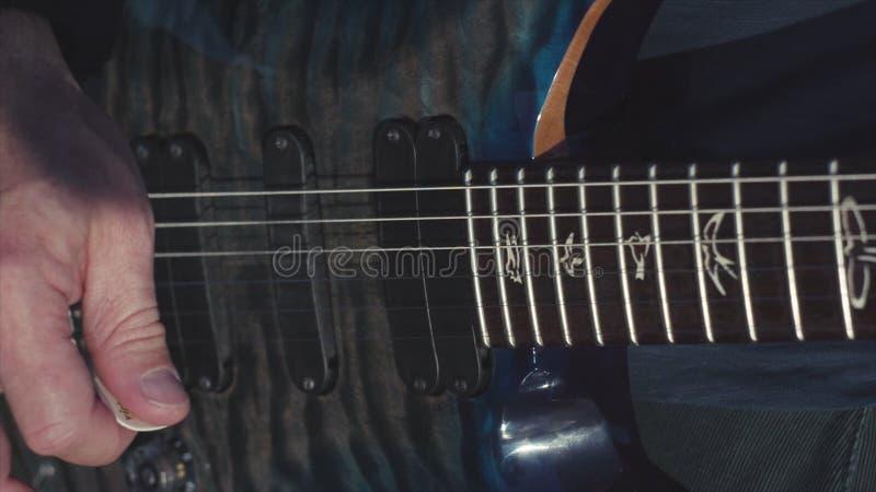 Close-up die van handen basgitaar spelen voorraad Mannelijke handen van gitarist het spelen snaren op basgitaar uitgevoerde muzie stock afbeelding
