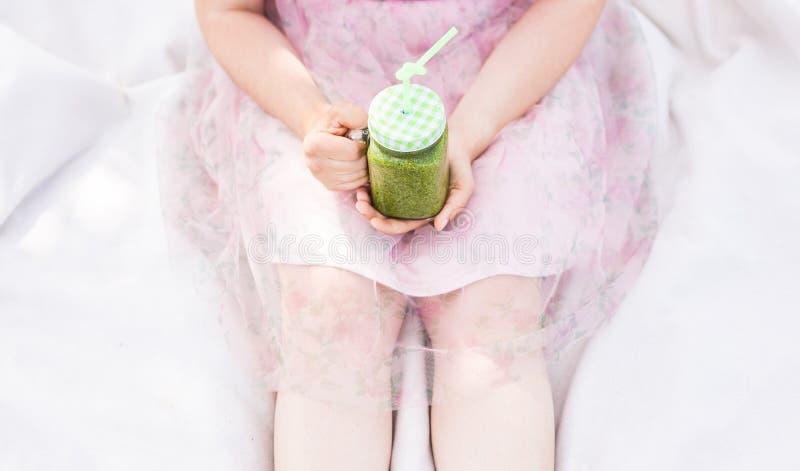Close-up die van Jonge vrouw groene smoothies houden bij een picknick Gezond voedsel, detox en dieetconcept stock afbeelding