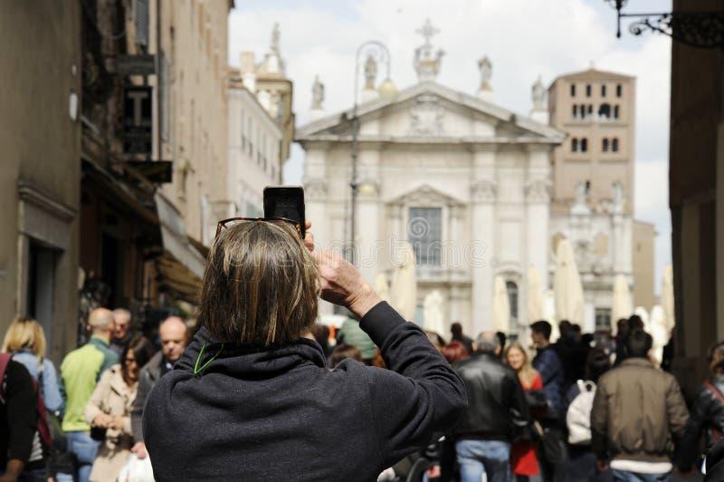 Close-up die van mensentoerist op de straat in Mantua, foto van Piazza Sordello met de telefoon nemen Mantua, Itali? royalty-vrije stock fotografie