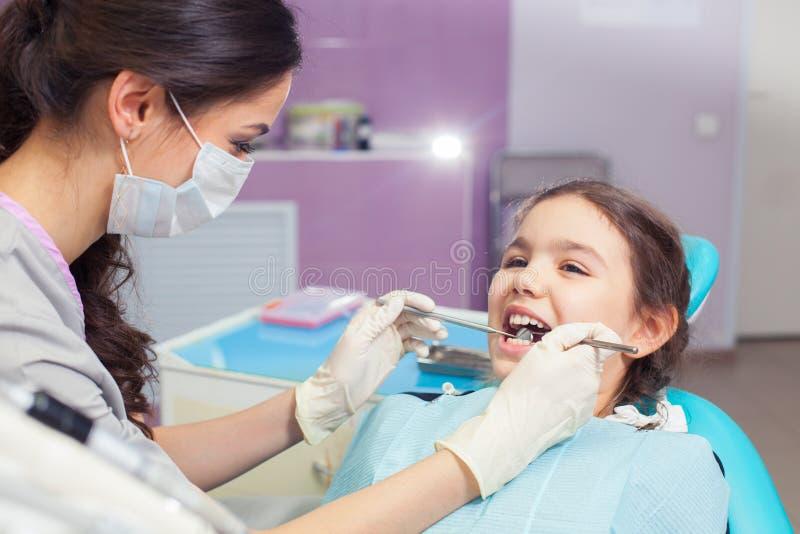 Close-up die van mooi meisje zijn mond openen wijd tijdens het behandelen van haar tanden door de tandarts stock afbeelding