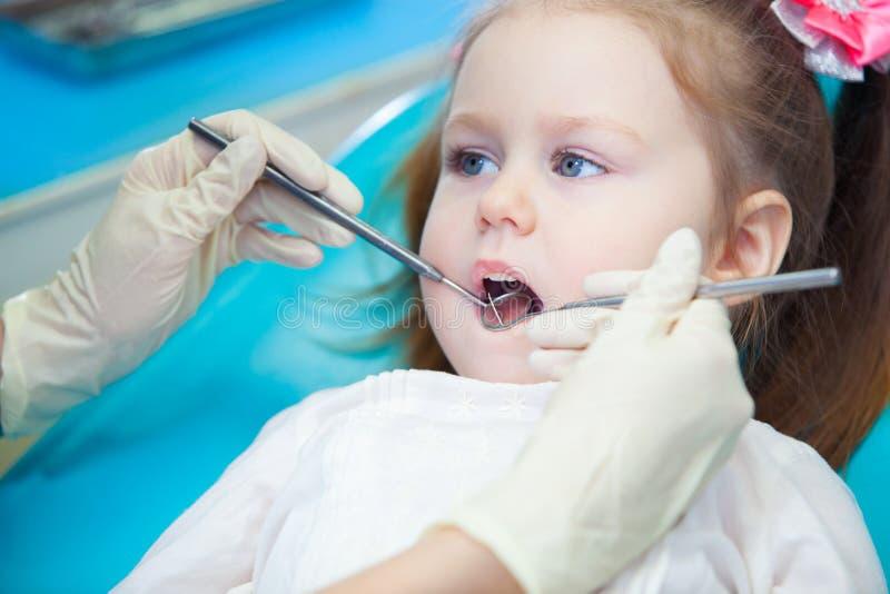 Close-up die van mooi meisje zijn mond openen wijd tijdens inspectie van mondholte bij de tandarts royalty-vrije stock foto