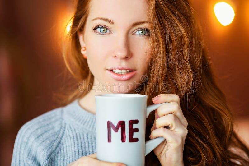 Close-up die van mooie vrouwelijke handen een grote glaskop van koffiecappuccino houden Vrouw die de warme gebreide winter dragen royalty-vrije stock foto's