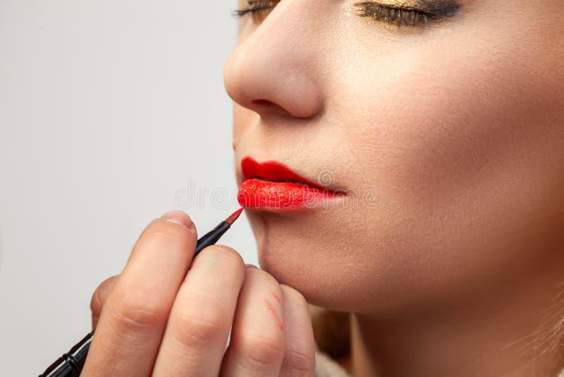 Close-up die van samenstelling op de lippen van het model het van toepassing zijn, de grimeur houdt een borstel in haar hand en p stock foto