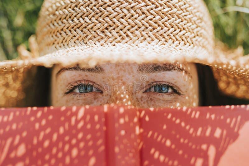 Close-up die van vrouw haar gezicht behandelen met een rood boek royalty-vrije stock fotografie