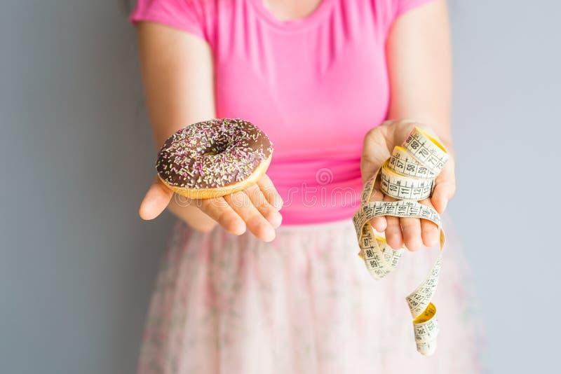 Close-up die van vrouwen` s handen een doughnut en een metende band houden Het concept het gezonde eten Dieet royalty-vrije stock foto's