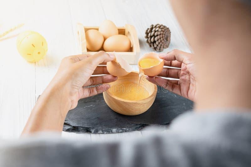 Close-up die van vrouwenchef-kok een ei breken in de houten kom Cooki stock foto's