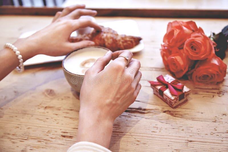 Close-up die van vrouwenhanden vers croissant in koffie houden, vierend Valentine ` s Dag, verjaardag Boeket van bloemen op houte stock foto's