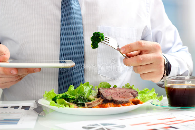Close-up die van zakenman die aan marketing strategie tijdens bedrijfslunch werken, sappig clublapje vlees eten stock afbeelding