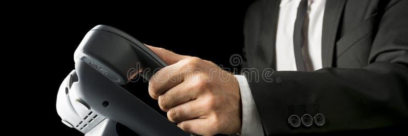 Close-up die van zakenman een zwarte landline telefoon opnemen aangaande stock afbeelding