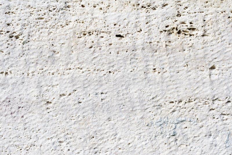 Close-up Diepe textuur van wit-geschilderde poreuze steen op de voorgevel van het gebouw Gestenigde muurtextuur als achtergrond stock foto's
