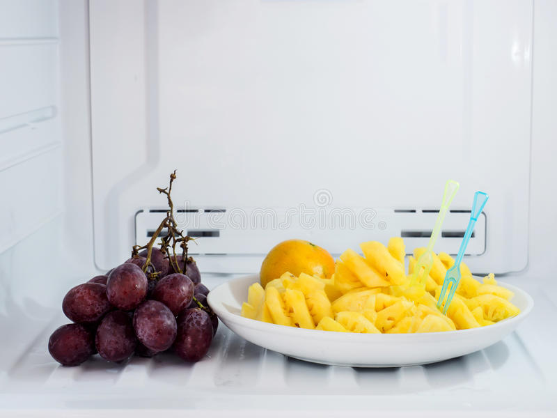 Close up of diet fruits, pineapple and orange dish with grape pu. T on the freezer fridge (refrigerator royalty free stock images