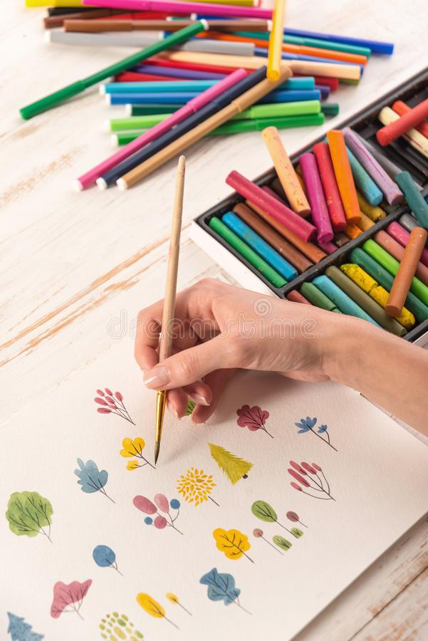 Side view of artist drawing flowers design at workplace. Close up of different colorful flowers nature design painted with brush and watercolors on paper royalty free stock images
