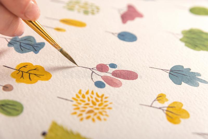 Side view of artist drawing flowers design at workplace. Close up of different colorful flowers nature design painted with brush and watercolors on paper stock image