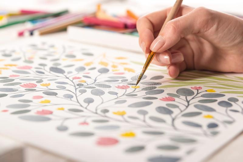 Side view of artist drawing flowers design at workplace. Close up of different colorful flowers nature design painted with brush and watercolors on paper royalty free stock photography