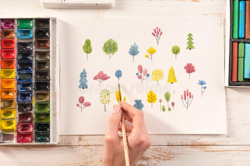 Side view of artist drawing flowers design at workplace. Close up of different colorful flowers nature design painted with brush and watercolors on paper royalty free stock photos