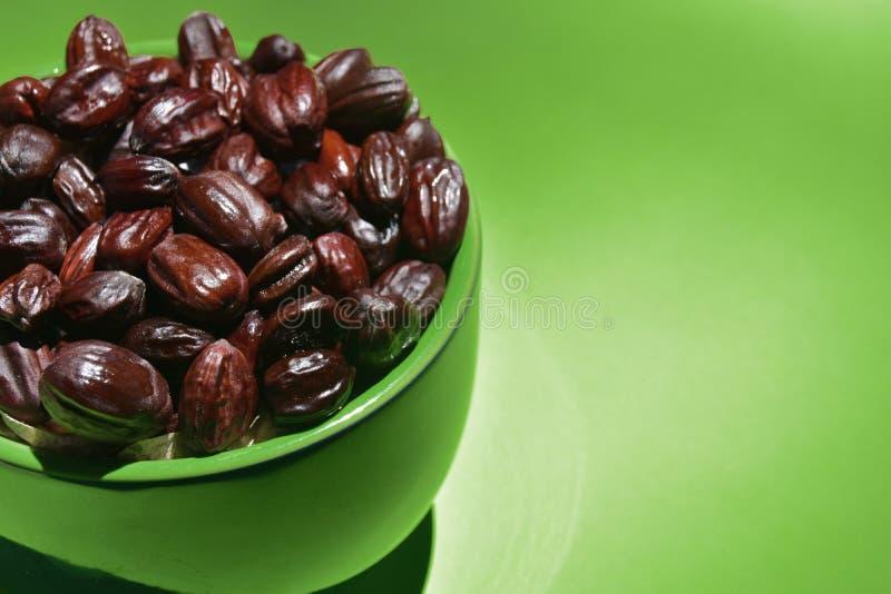 Jojoba seeds in a green bowl stock photos