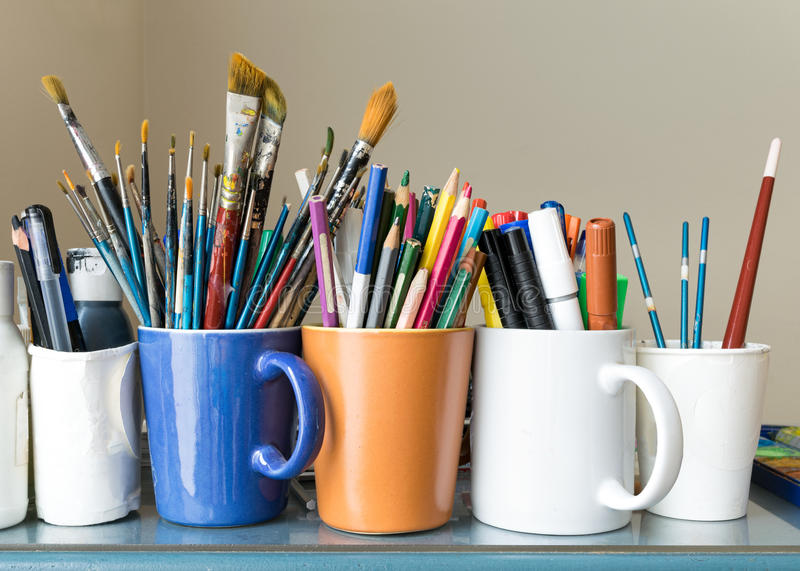 Close up of different used paint brushes, sharpened colored pencils, pens, and markers stock photography