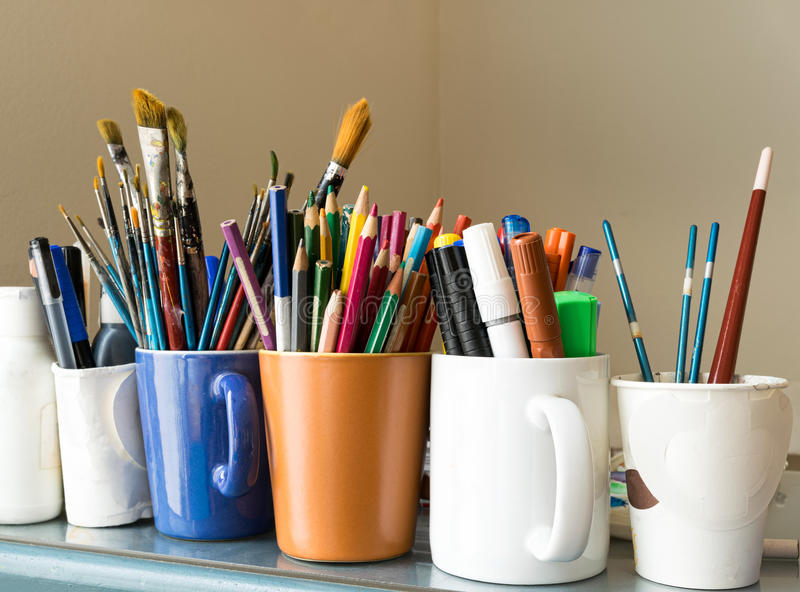 Close up of different used paint brushes, sharpened colored pencils, pens, and markers. On colored mugs over blue table and beige background royalty free stock photography