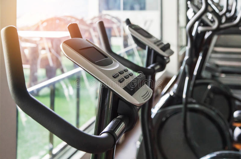 Close up digital display screen control exercise bike equipment in fitness room center stock photography