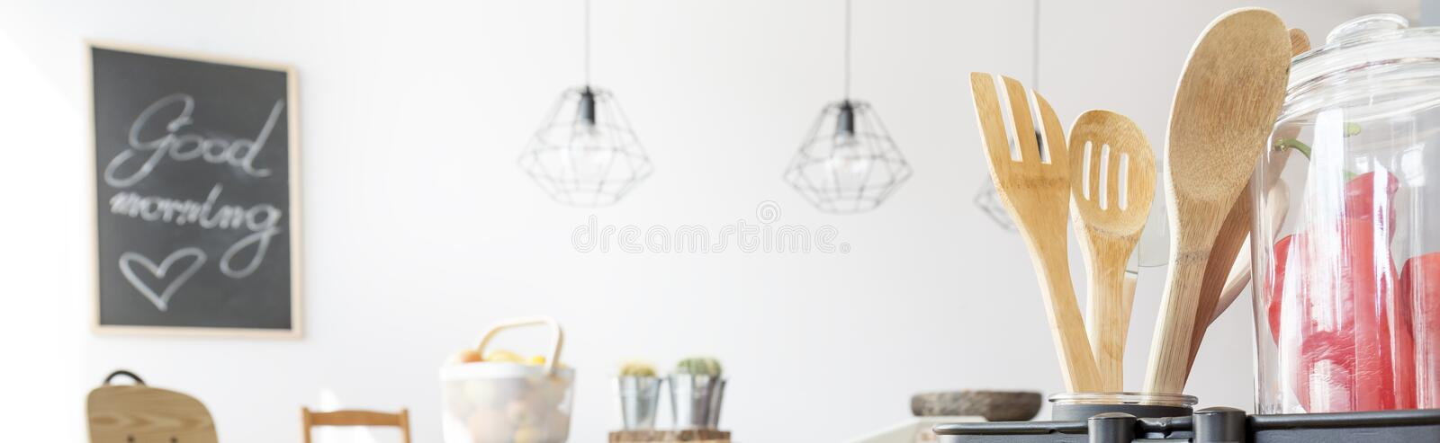 Close-up of dining area. With wooden cutlery and black board on a wall royalty free stock photo