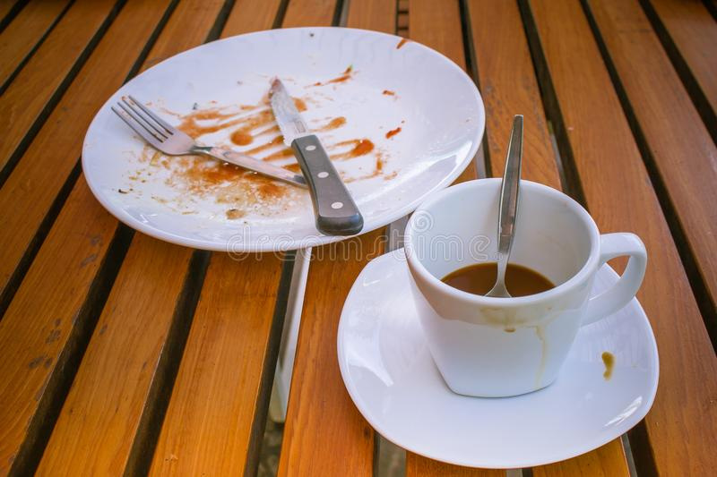Close up dirty coffee cup and spoon setting on white saucer, knife and fork on white dirty dish. They are on wooden table. stock photos