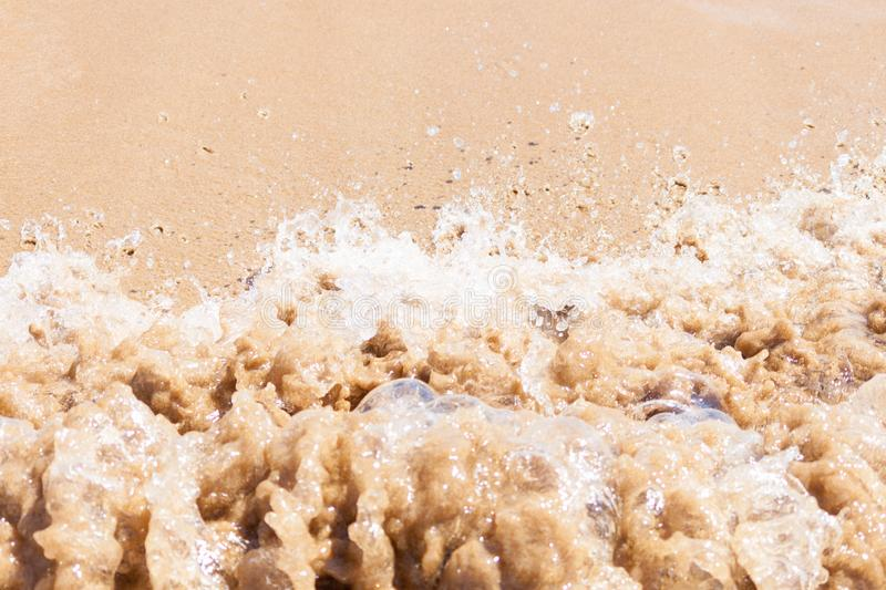Close up of dirty wave of sea or ocean on sandy beach. Background stock photography