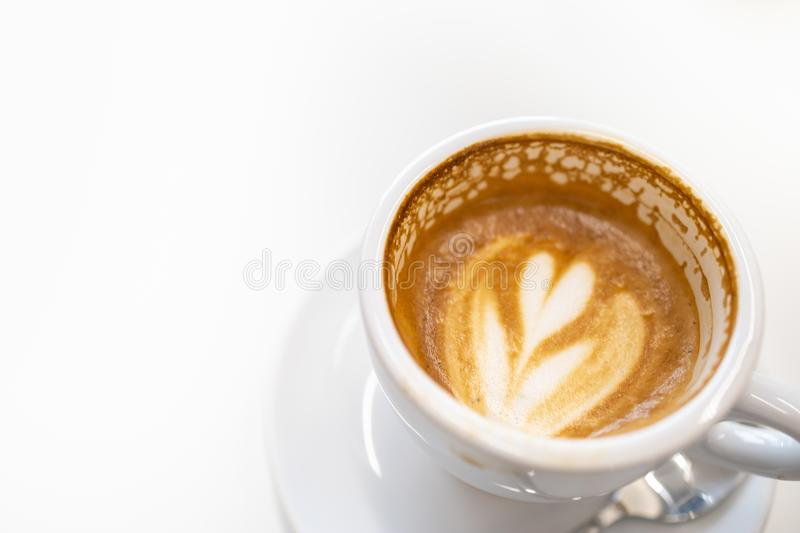 Close up of dirty white cup of hot coffee latte with heart shape art and white plate and spoon on with copy space for text royalty free stock photos