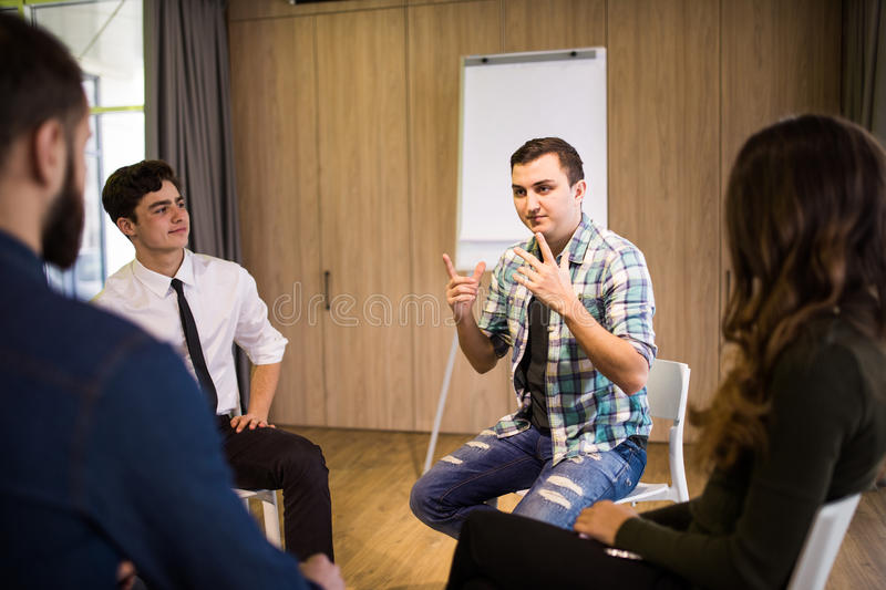 Close-up on discussion. Close-up of people communicating while sitting in circle and gesturing stock photo