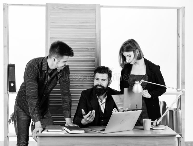Close-up on discussion. Discussion group working and communicating at office desk together with colleagues. Professional stock image