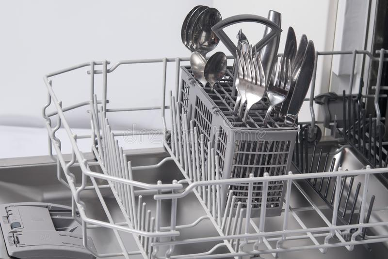Close-up of a dishwasher container, with cutlery, forks, spoons, knives, after work royalty free stock photo