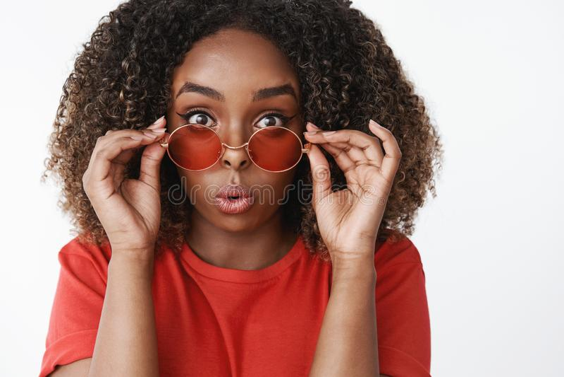 Close-up disparado da menina afro-americano feminino atrativa surpreendida e divertida com cabelo encaracolado que decola óculos  foto de stock
