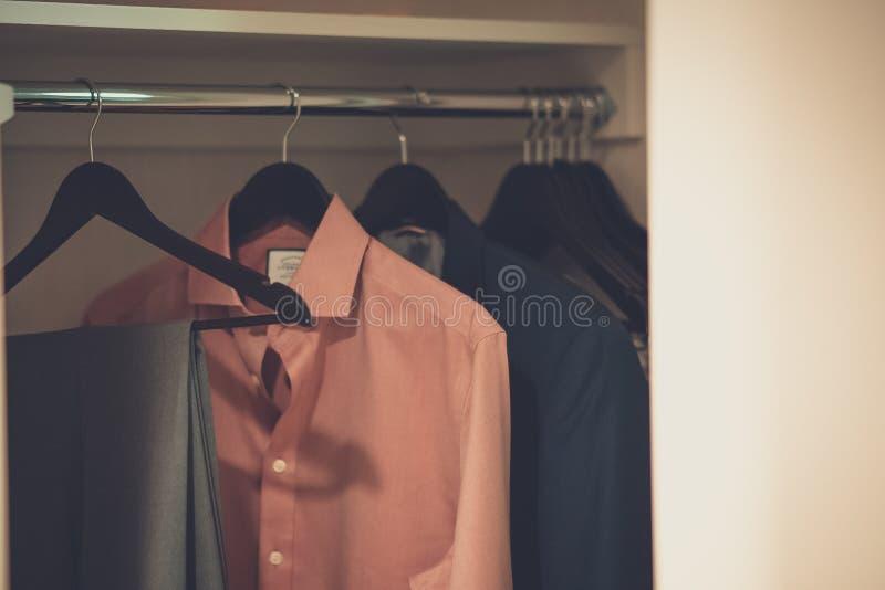Close up disparado da roupa masculina pendurada em ganchos em um vestuário fotografia de stock royalty free