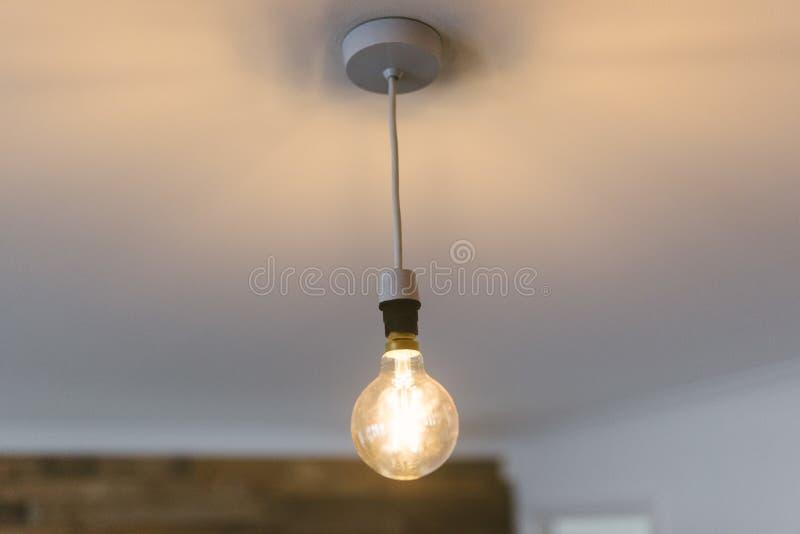 Close up disparado de uma grande ampola iluminada que pendura do teto imagens de stock royalty free