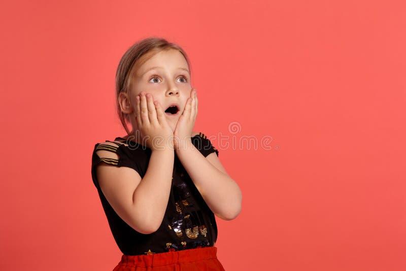 Close-up disparado de uma senhora pequena loura encantador em um vestido combinado que levanta contra um fundo cor-de-rosa imagens de stock