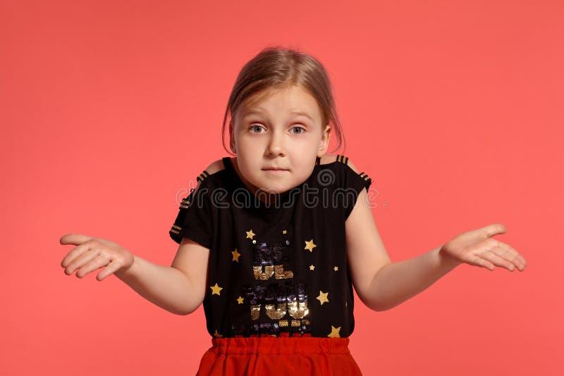 Close-up disparado de uma senhora pequena loura encantador em um vestido combinado que levanta contra um fundo cor-de-rosa foto de stock